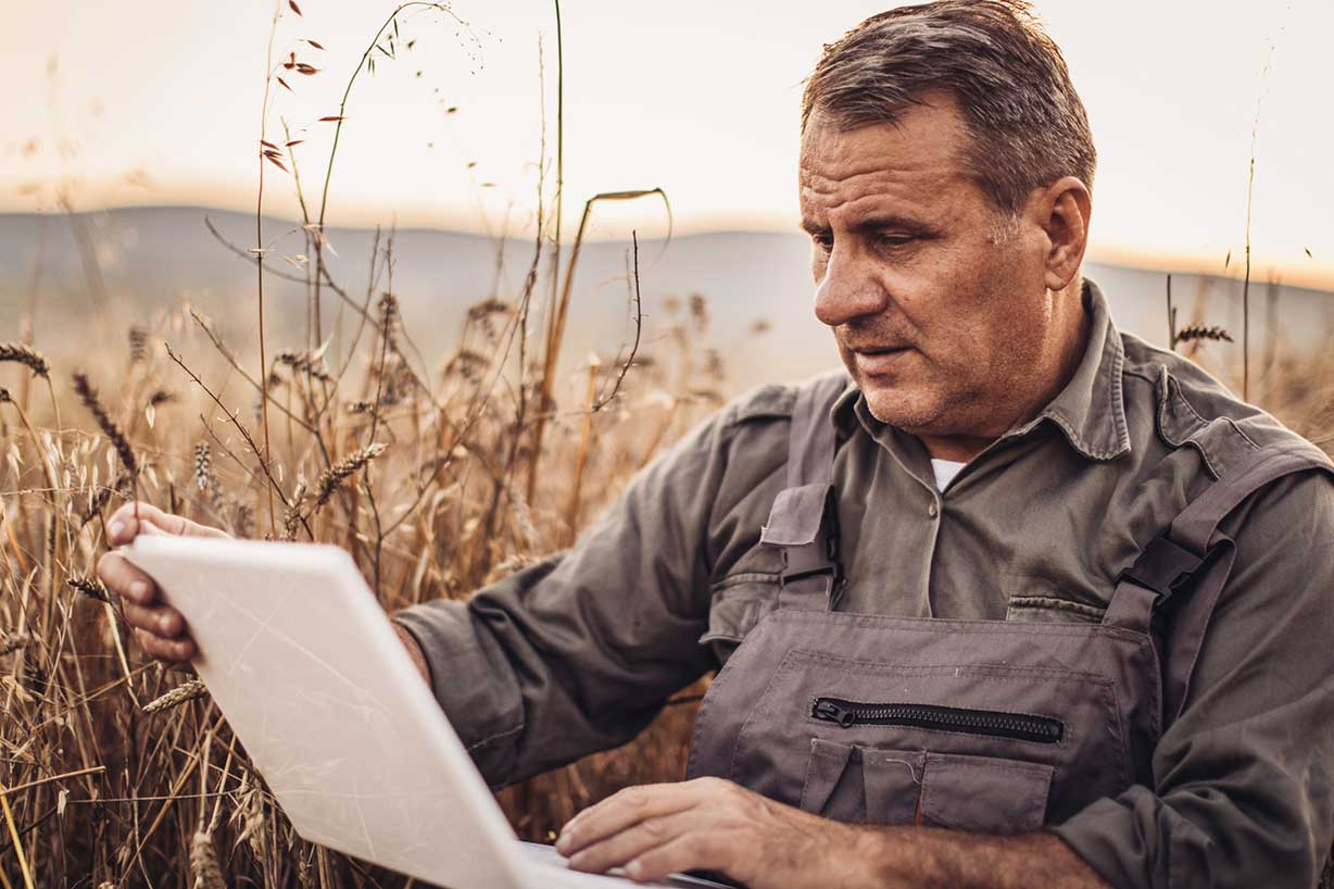 A farmer in a field checking his laptop to make sure transportation is running smoothly