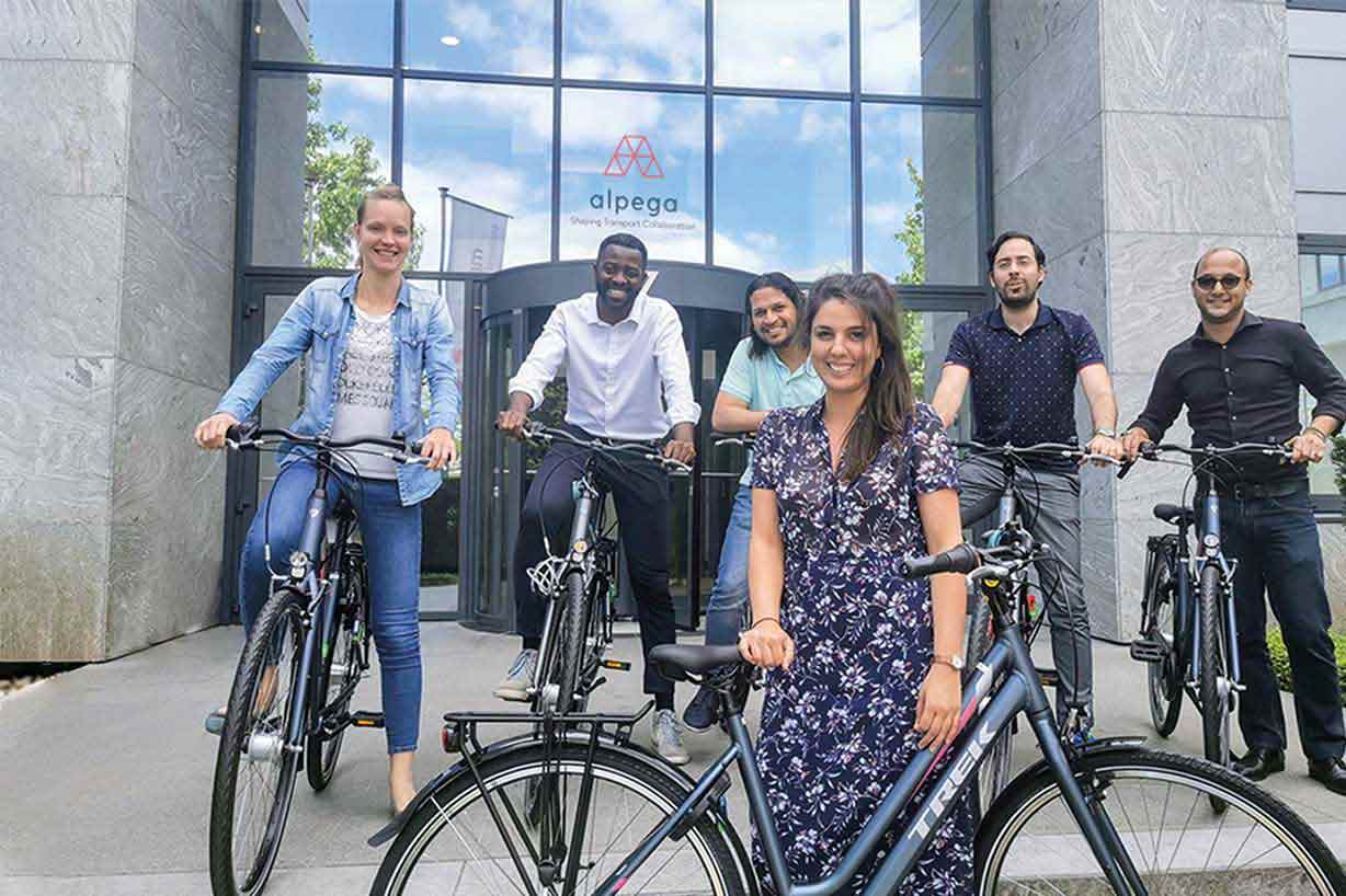 Six happy Alpega employees trying out their new company bikes in front of an Alpega office